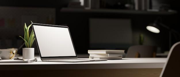 深夜の作業スペースは、事務用品を備えた暗い部屋の装飾の光の下でラップトップを開きます