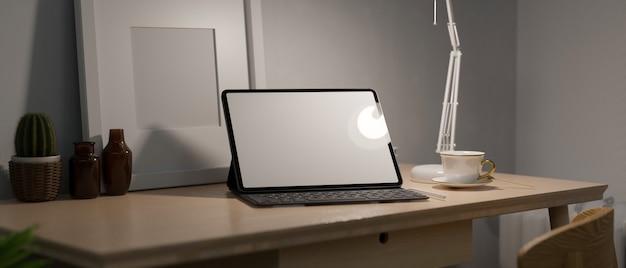 タブレットとフレームが空白の画面にある夜間の作業スペースランプからの低照度自宅での夜の仕事