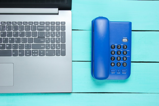 Work space call center. laptop, office phone on a blue wooden table.
