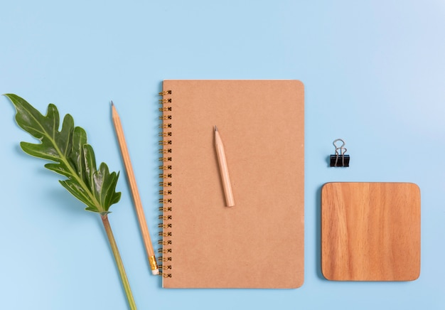 Work space composition with notebook, brown pencil, wood plate and green leaves, top view