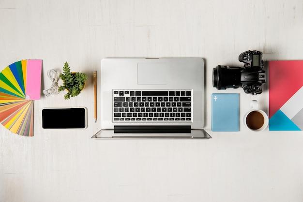 사진 작가, 그래픽 디자이너를 위한 작업 공간. 노트북, 카메라, 컬러 차트, 디지털 태블릿, 커피 컵, 책, 연필이 나무 테이블에 평평하게 놓여 있습니다.