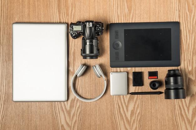 Рабочее место для фотографа, графического дизайнера. плоская планировка ноутбука, фотоаппарата, цветной диаграммы, цифрового планшета, кофейной чашки, книги, карандаша на деревянном столе.
