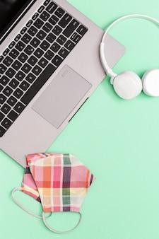 Рабочее место для работы или учебы с серым ноутбуком и средствами индивидуальной защиты.