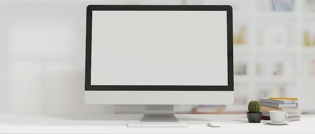 空白の画面の本のサボテンとコーヒーカップのデスクトップコンピュータと最小限のスタイルの装飾の作業スペース