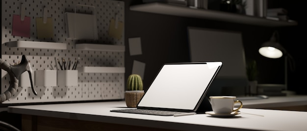 Work space at night tablet empty screen on white table decor with stationery office in evening