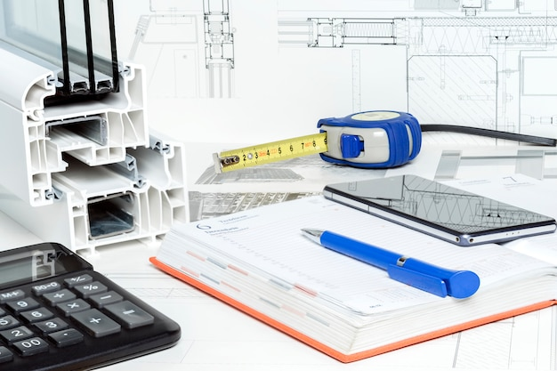 Work space table with notepad, pen, tape measure, calculator,