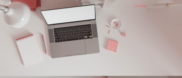 ピンクのペーパークリップのメモ帳とピンクの文房具を備えたコピースペースの空白の画面のラップトップを備えた作業スペース