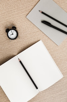 Work space with noteboook and pen near clock Premium Photo