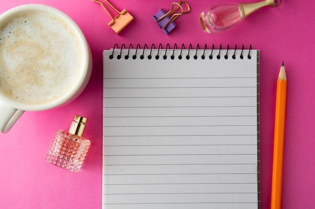Рабочее пространство, рабочий стол. открытая тетрадь, кофейная чашка и канцелярские товары. розовая плоская планировка, копия пространства.