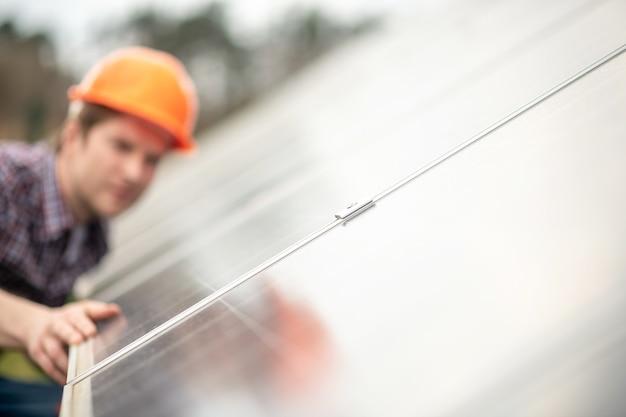 仕事の詳細。労働時間中に新鮮な空気の中で特別なデザインの平らな鏡の表面の近くの保護明るいヘルメットの男