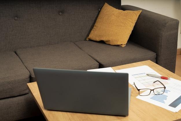 Рабочий стол дома с ручкой, бумагами, счетами, диаграммами, очками, компьютером и калькулятором. концепция работы на дому, текущие счета, экономика дома. вид под углом 45 градусов или порезанный.