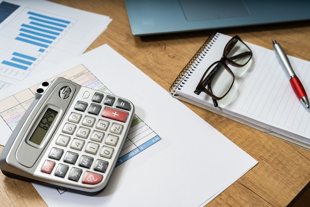 ペン、紙、請求書、チャート、メガネ、コンピューター、電卓を備えた自宅の作業台。在宅勤務、当座預金口座、家の経済。 45度またはみじん切りを表示します。