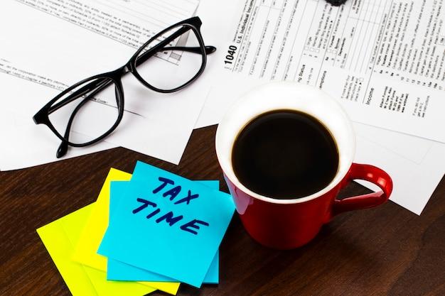 書類と一杯のコーヒーで覆われた作業テーブル、および税の時間の碑文と付箋