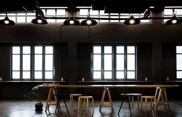 큰 창문이있는 어두운 로프트 카페 디자인의 작업 테이블