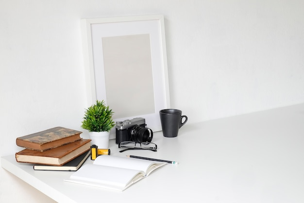Work table with photography camera, book, notepad and pencil on table and empty photo frame.