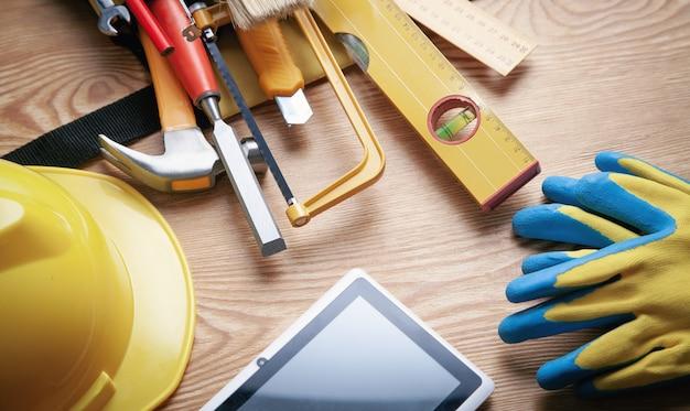 木製の背景にヘルメット、タブレット、手袋で作業ツール。