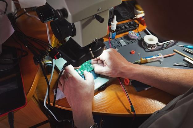 Работайте под микроскопом. устройство микроэлектроники. крупным планом руки обслуживающего работника, ремонтирующего современный смартфон. концепция ремонта и обслуживания.