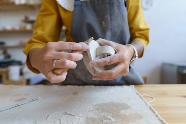 항아리를 준비하기 위해 원시 점토 여성 도자기 스튜디오 소유자 성형 및 모델링 재료 작업
