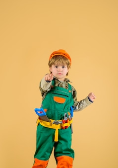 Work with tools repair little boy in builder uniform with tools belt little kid repairman pointing
