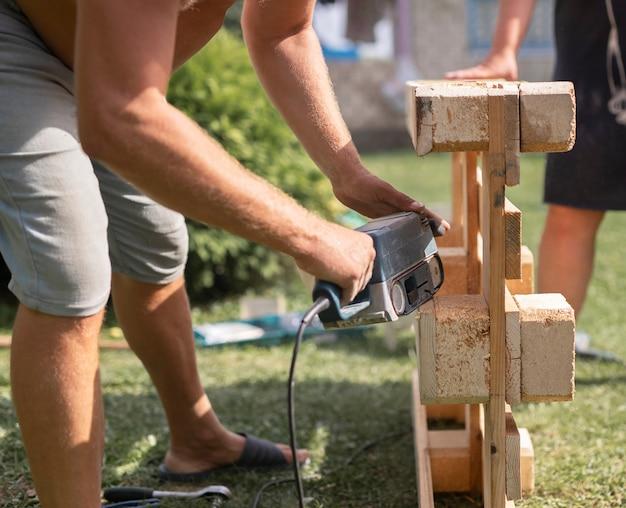 屋外の自然の中で木製の家具を作る木のコンセプトで作業する