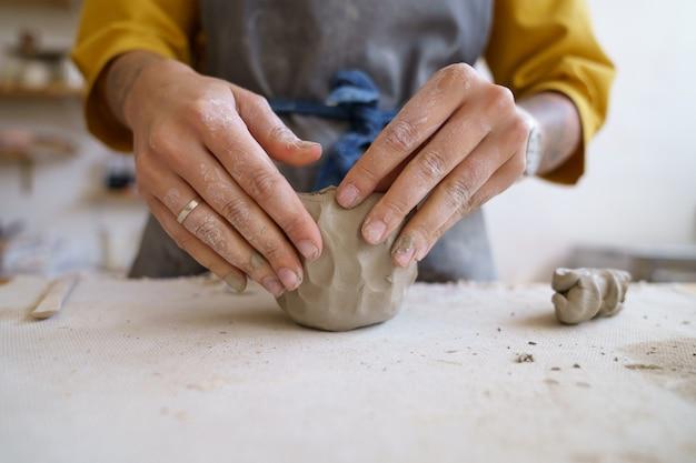 도자기 또는 도자기 조각 및 형성을 위해 원시 점토를 성형하는 손 예술가 여성과 함께 작업