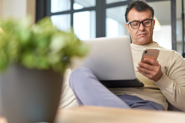 Work in your comfort zone handsome latin middle aged businessman in eyeglasses using smartphone