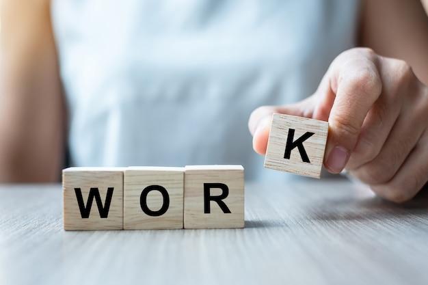 Workビジネス単語の木製キューブブロックを持っている実業家の手。ハードワークとライフバランスの概念