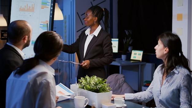Афро-американский лидер трудоголик стоит перед монитором презентации и объясняет маркетинговые пр ...