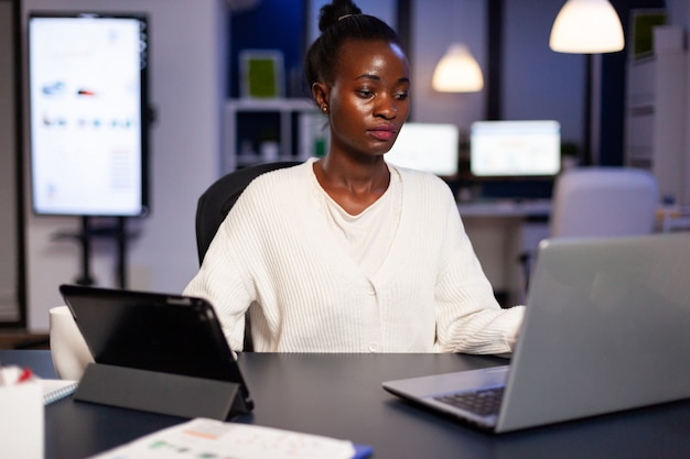 Workaholic african manager trying to finish deadline checking charts on tablet pc and laptop