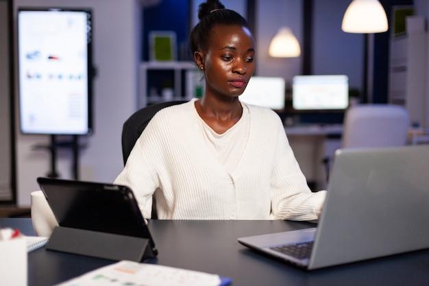 태블릿 pc 및 노트북에서 마감 시간 확인 차트를 완료하려고 하는 워커홀릭 아프리카 관리자