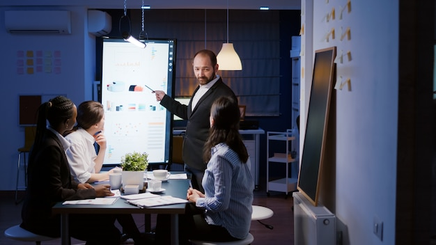 Workaholic businessman brainstorming marketing strategy overworking in company meeting office room late at night. diverse multi-ethnic businesspeople looking at financial presentation on monitor