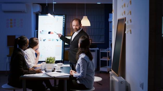 워커홀릭 사업가는 늦은 밤 회사 회의실에서 과로하는 마케팅 전략을 브레인스토밍합니다. 모니터에서 재무 프레젠테이션을 보고 있는 다양한 다민족 기업인