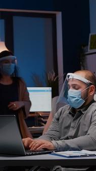 Uomo d'affari maniaco del lavoro con maschera facciale e visiera contro il covid che lavora nell'ufficio dell'azienda