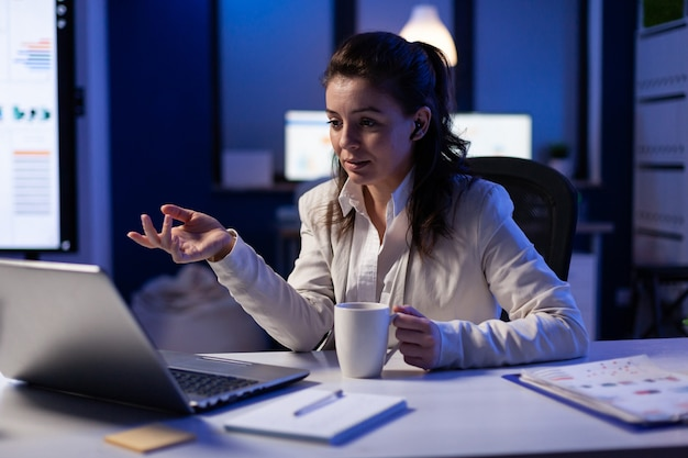 Workaholic businesswoman analysing economic statistics late at night in business office. tired woman planning marketing project before deadline using modern technology network wireless