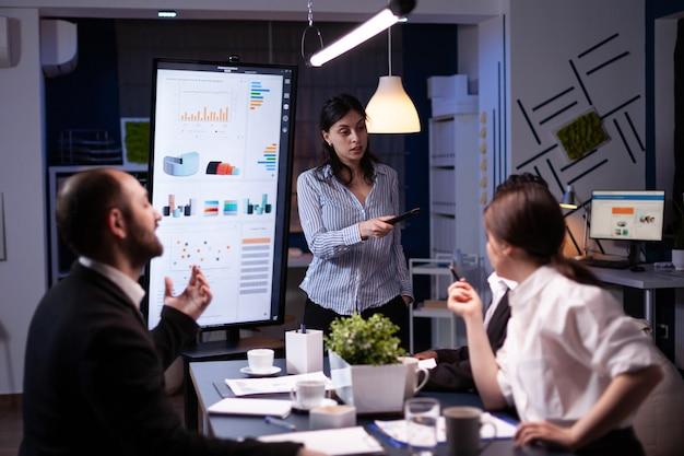 회사 회의실에서 초과 근무하는 모니터를 사용하여 재무 전략을 가리키는 워커홀릭 여성. 다양한 다민족 팀워크로 저녁에 관리통계 풀기