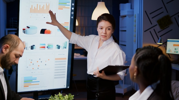 Workaholic businesswoman presenting company solution using presentation monitor