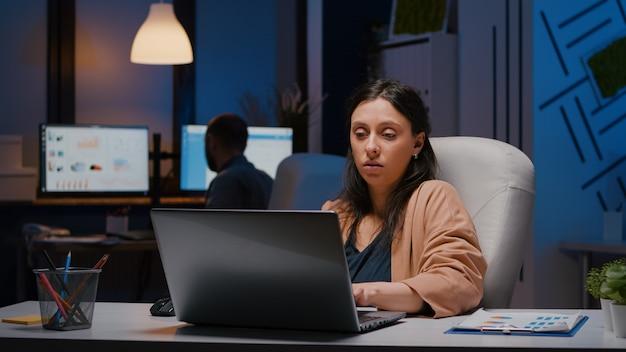 금융 그래픽을 분석하는 책상 테이블에 앉아 일 중독적인 기업가 여성