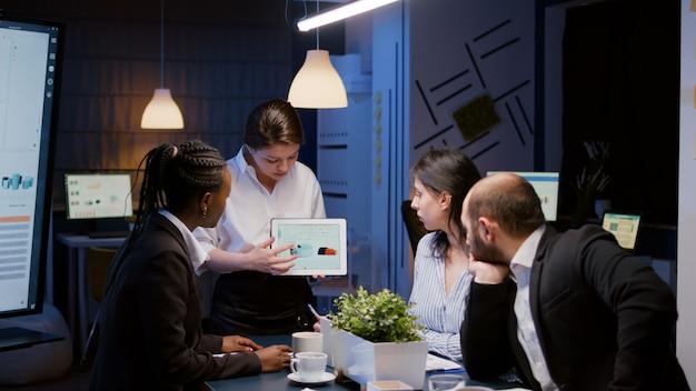 늦은 밤 비즈니스 사무실 회의실에서 과로하는 회사 그래프를 설명하는 태블릿을 들고 일중독에 빠진 여성 사업가입니다. 저녁에 통계 문제를 해결하는 다양한 다민족 동료