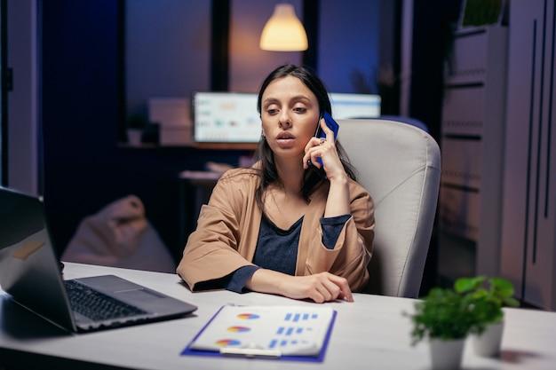 Менеджер-трудоголик разговаривает с клиентом по телефону вечером. женщина-предприниматель, работающая поздно ночью в корпоративном бизнесе, делает сверхурочную работу во время телефонного звонка.