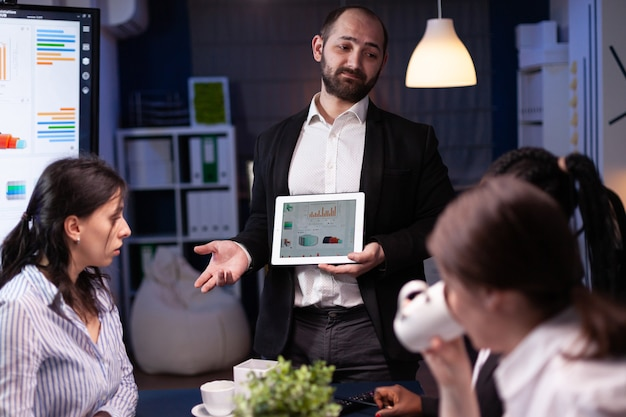 Workaholic overworked businessman explaining company strategy using tablet for presentation working overtime in meeting office room late at night. diverse multi-ethnic teamwork brainstorming ideas.