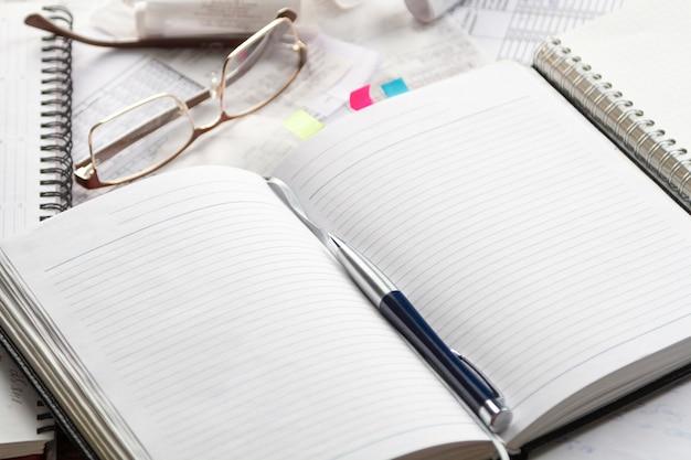 Рабочая тетрадь, авторучка, очки, финансовые документы на офисном столе.