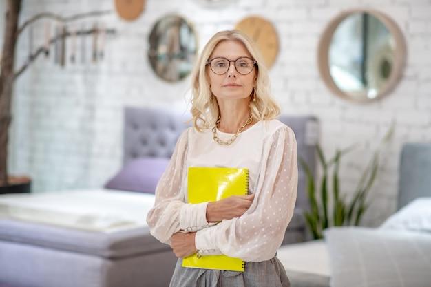 ワークブック。家具店のサロンに立っているノートの黄色いノートをつかんで深刻なビジネス女性。