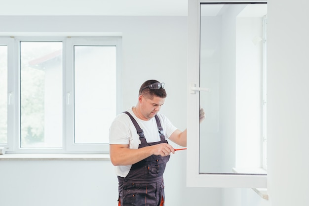 The worker adjusts the window in the apartment of the house after repair