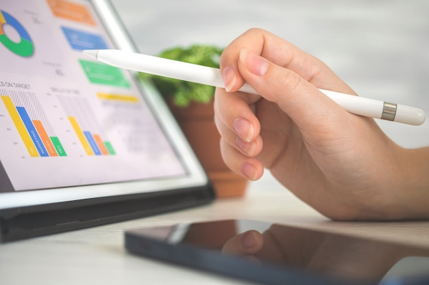 Worker analyzing company perfomance on digital tablet pc using stylus pen. business and financial diagram on the screen, office desk background photo