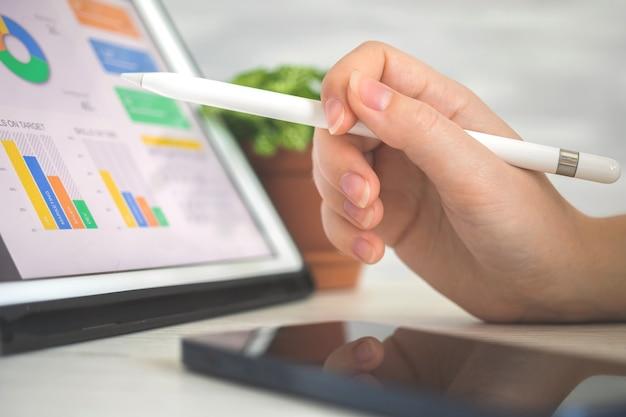 작업자가 스타일러스 펜을 사용하여 디지털 태블릿 pc에서 회사 성과를 분석합니다. 화면의 비즈니스 및 재무 다이어그램, 사무실 책상 배경 사진
