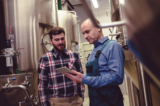 醸造所でデジタルタブレットについて議論する労働者および所有者
