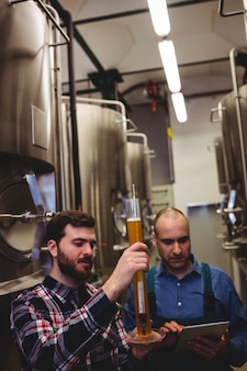 醸造所でビールを検査する労働者と所有者