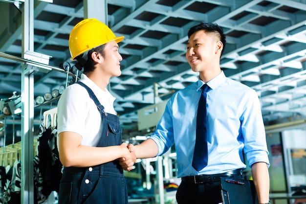 Рабочий и начальник производства на заводе
