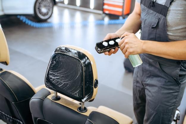 Рабочий наносит средство на щетку, химчистку автокресла и детализацию