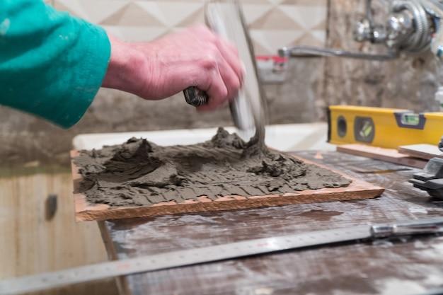 Рабочий наносит цементный клей на плитку. технология укладки плитки.